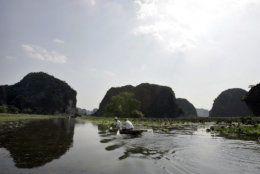A boat passes through Tam Coc in Ninh Binh Province, about 100 kilometer ( 62 miles) from Hanoi, Vietnam, Wednesday, Sept. 19, 2007. Tam Coc, which means three caves, is also referred to as Halong Bay on Land. Tourists often used boats to explore the caves on the river. (AP Photo/Chitose Suzuki)