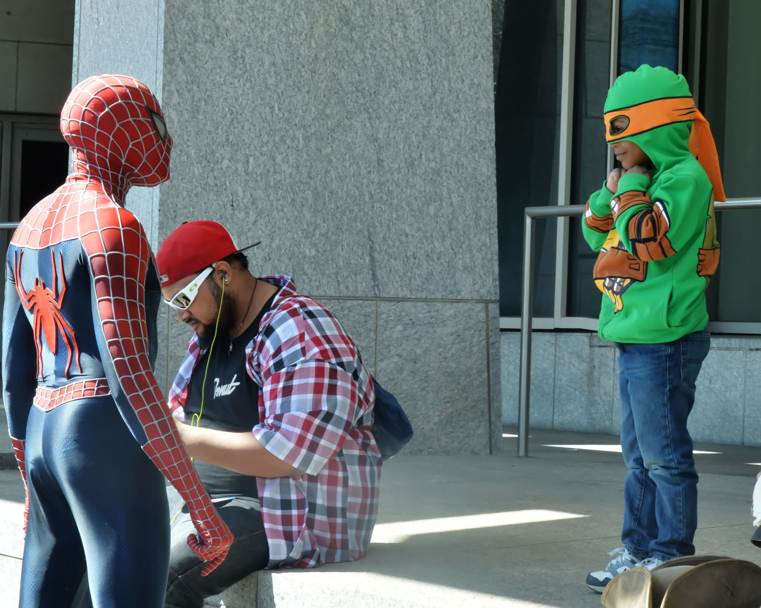 "A young boy dressed as a character from the ""Teenage Mutant Ninja Turtles"" comic book and movie series smiles as he meets Spider Man at Awesome Con 2018 at the Walter E. Washington Convention Center in Washington, D.C. (Shannon Finney)"