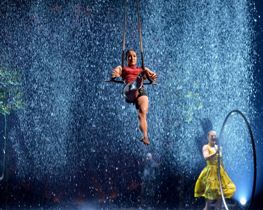 An acrobat performs her routine with an onstage rainstorm as a backdrop.