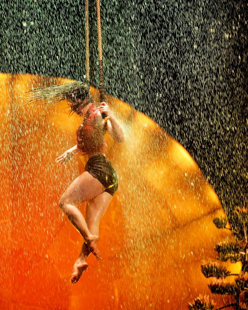 An acrobat performs her routine with an onstage rainstorm as a backdrop. (Courtesy Shannon Finney)