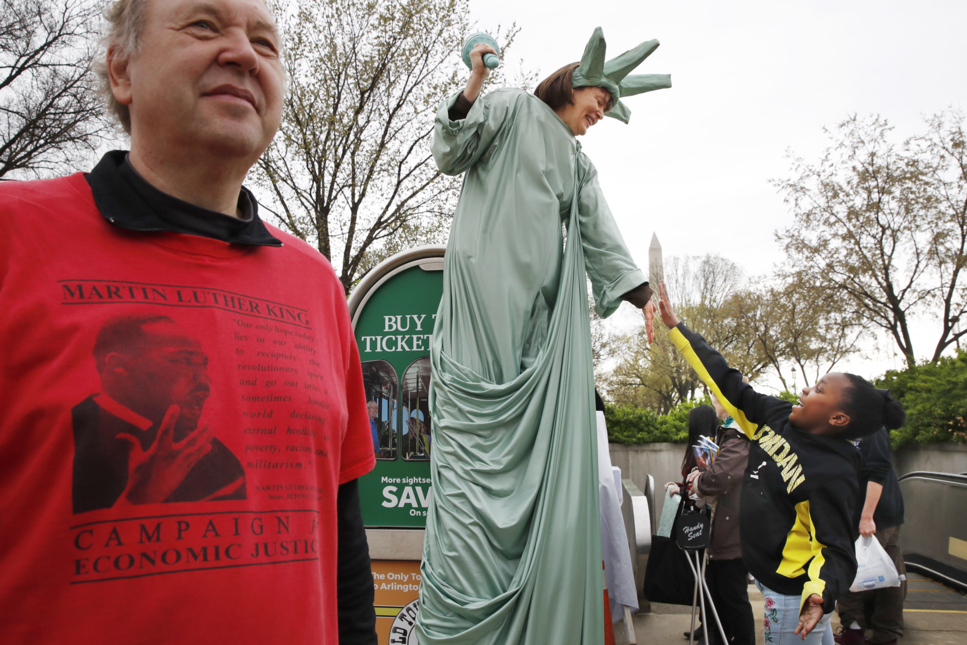 """Debbie Davis, of Milwaukee, Wisc., dressed on stilts as """"lady liberty,"""" gets a high five from Trinity Mitchell, 8, of Canton, Ohio, as they attend the A.C.T. To End Racism rally, Wednesday, April 4, 2018, on the National Mall in Washington, on the 50th anniversary of Martin Luther King Jr.'s assassination. At left is Art Laffin, of Washington. (AP Photo/Jacquelyn Martin)"""