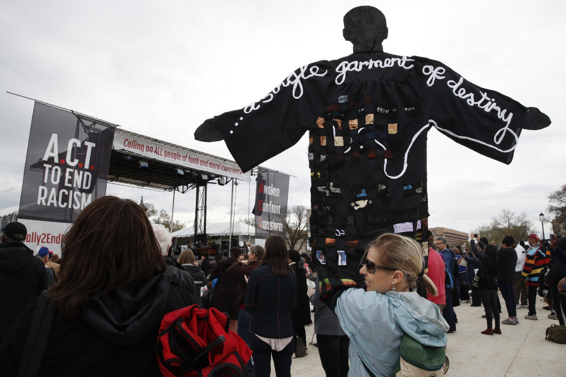 Molly Jackman, of Kensington, Md., holds up a sign with a silhouette of Martin Luther King Jr., while attending the A.C.T. To End Racism rally, Wednesday, April 4, 2018, on the National Mall in Washington, on the 50th anniversary of King's assassination. (AP Photo/Jacquelyn Martin)