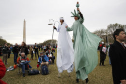 """Carolyn McCarthy, dressed on stilts as """"Lady Justice,"""" left, and Debbie Davis, dressed as """"Lady Liberty,"""" both of Milwaukee, Wisc., attend the A.C.T. To End Racism rally, Wednesday, April 4, 2018, on the National Mall in Washington, on the 50th anniversary of Martin Luther King Jr.'s assassination. (AP Photo/Jacquelyn Martin)"""