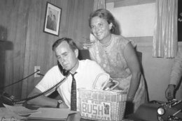 George Bush, candidate for the Republican nomination for the U.S. Senate, gets returns by phone at his headquarters in Houston, Saturday, June 6, 1964 as his wife Barbara, beams her pleasure at the news. Bush was leading his opponent Jack Cox in the run-off primary. Bush will face Sen. Ralph Yarborough (D-Tex) in the November general election if his lead holds and he is the winner. (AP Photo/Ed Kolenovsky)