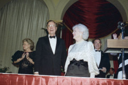 President-elect George H. W. Bush, left, and his wife, Barbara, right, smile at well-wishers during their second inaugural ball of the evening at the Pension Building, Jan. 18, 1989, Washington, D.C. (AP Photo/Marcy Nighwander)