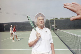 """First lady Barbara Bush pokes fun at herself by crossing her eyes for reporters who were visiting the summer White House in Kennebunkport, Maine, August 23, 1989. When asked about her health and recent treatment for Graves's disease, which affects her vision, Mrs. Bush replied, """"I want you to see my eye's are just fine."""" (AP Photo/Pat Wellenbach)"""