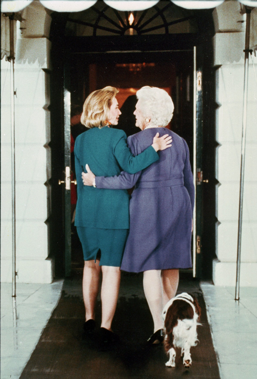 First lady Barbara Bush, right,  gives incoming first lady Hillary Rodham Clinton a tour of the White House as the Bush's springer spaniel Millie follows, Nov. 19, 1992.  (AP Photo/Ron Edmonds)