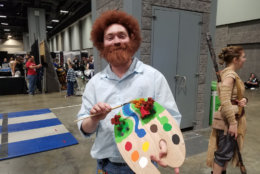 A man dressed as painter Bob Ross with several happy little trees on his palette. (WTOP/Will Vitka)