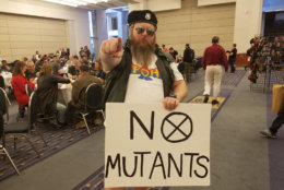 A man holds a sign espousing anti-mutant views at AwesomeCon 2018. (WTOP/Will Vitka)
