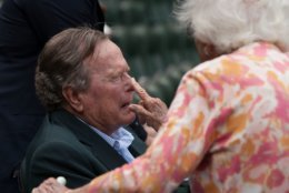 """FILE - In this May 3, 2015, file photo, Barbara Bush applies sunscreen to the nose of her husband, former President George H.W. Bush, before the Seattle Mariners take on the Houston Astros in a baseball game in Houston, Texas. Former first couple George and Barbara Bush's relationship is a true love story, described by granddaughter Jenna Bush Hager as """"remarkable."""" They met at a Christmas dance. She was 17. He was 18. Two years later they were married. Now 73 years later, with Barbara Bush declining further medical care for health problems, they are the longest-married couple in presidential history. (AP Photo/George Bridges, File)"""