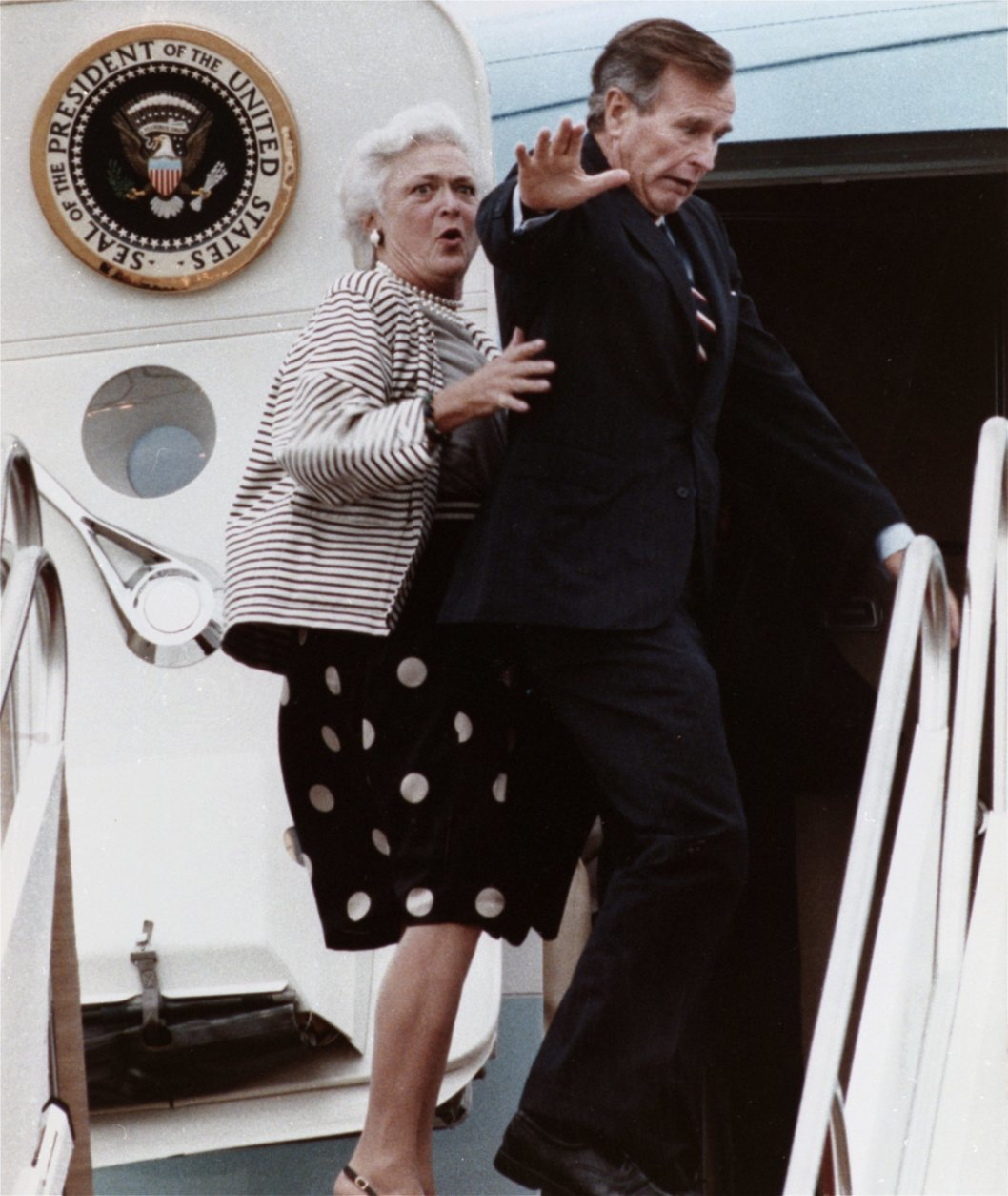 """FILE - In this Sept. 22, 1989, file photo, first lady Barbara Bush reacts after President George H.W. Bush accidentally stepped on her toe while boarding Air Force One at Andrews Air Force Base, Md., for a flight to New Jersey. Former first couple George and Barbara Bush's relationship is a true love story, described by granddaughter Jenna Bush Hager as """"remarkable."""" They met at a Christmas dance. She was 17. He was 18. Two years later they were married. Now 73 years later, with Barbara Bush declining further medical care for health problems, they are the longest-married couple in presidential history. (AP Photo/Charles Tasnadi, File)"""