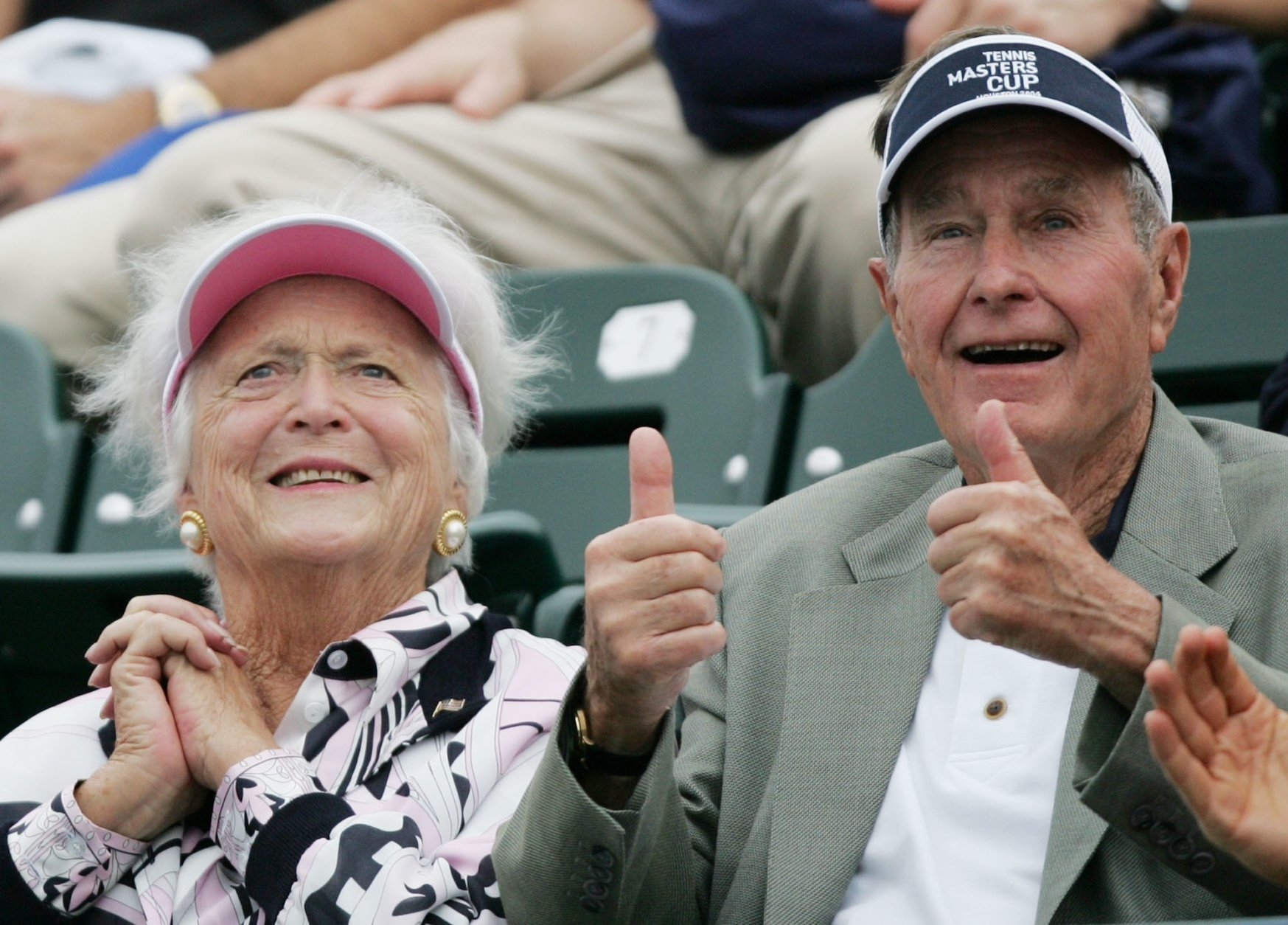"""FILE - In this Nov. 16, 2004 file photo, former President George Bush, right, gives a thumbs-up while he and his wife, Barbara, left, attend the Tennis Masters Cup tournament in Houston. With her husband still at her side, Barbara Bush has decided to decline further medical treatment for health problems and focus instead on """"comfort care"""" at their home in Houston. Family spokesman Jim McGrath disclosed Barbara Bush's decision Sunday, April 15, 2018. (AP Photo/David J. Phillip, File)"""