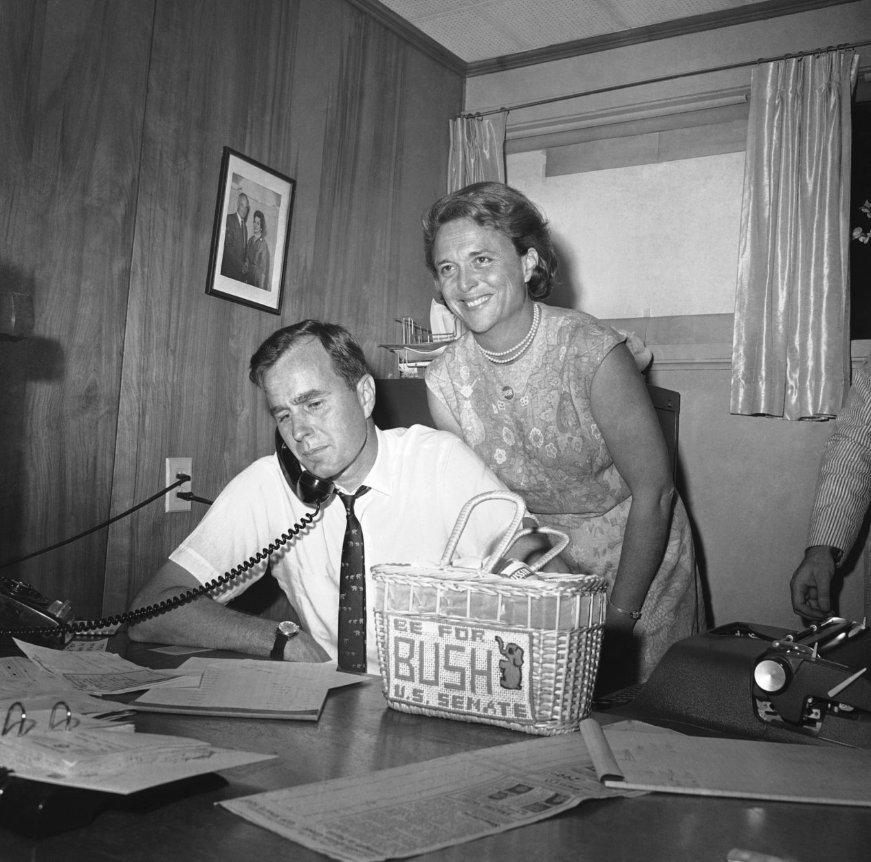 """FILE - In this June 6, 1964 file photo, George Bush, candidate for the Republican nomination for the U.S. Senate, gets returns by phone at his headquarters in Houston as his wife Barbara, beams her pleasure at the news. Former first couple George and Barbara Bush's relationship is a true love story, described by granddaughter Jenna Bush Hager as """"remarkable."""" They met at a Christmas dance. She was 17. He was 18. Two years later they were married. Now 73 years later, with Barbara Bush declining further medical care for health problems, they are the longest-married couple in presidential history. (AP Photo/Ed Kolenovsky, File)"""