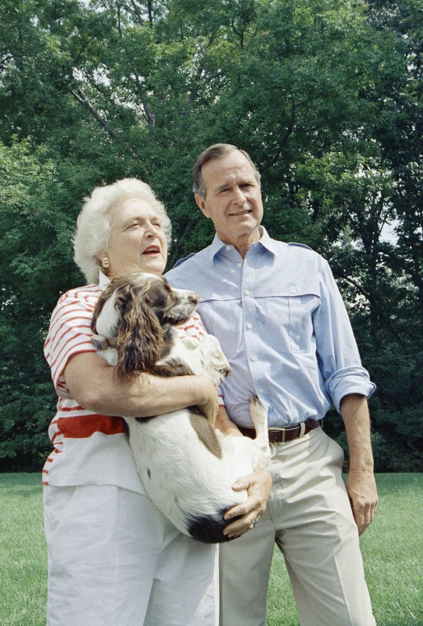 """FILE - In this Sept. 3, 1988 file photo, Vice President George H.W. Bush, right, and his Barbara Bush, holding the family dog, talk to reporters after a press conference outside their home in Washington, D.C. Former first couple George and Barbara Bush's relationship is a true love story, described by granddaughter Jenna Bush Hager as """"remarkable."""" They met at a Christmas dance. She was 17. He was 18. Two years later they were married. Now 73 years later, with Barbara Bush declining further medical care for health problems, they are the longest-married couple in presidential history. (AP Photo/J. Scott Applewhite, File)"""