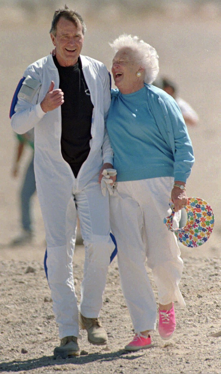 """FILE - In this March 25, 1997, file photo, former President George H.W. Bush gets a hug from his wife Barbara after he made a successful parachute jump at the U.S. Army's Yuma Proving Ground outside of Yuma, Ariz. Former first couple George and Barbara Bush's relationship is a true love story, described by granddaughter Jenna Bush Hager as """"remarkable."""" They met at a Christmas dance. She was 17. He was 18. Two years later they were married. Now 73 years later, with Barbara Bush declining further medical care for health problems, they are the longest-married couple in presidential history. (AP Photo/Mike Nelson, Pool, File)"""