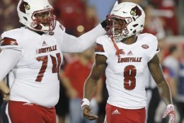 HOUSTON, TX - NOVEMBER 17: Offensive lineman Geron Christian #74 taps the head of quarterback Lamar Jackson #8 of the Louisville Cardinals while he walks off the field against the Houston Cougars in the second quarter at TDECU Stadium on November 17, 2016 in Houston, Texas. (Photo by Thomas B. Shea/Getty Images)