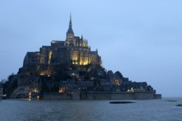 FILE - In this Friday, March 20, 2015 file photo, the Mont Saint-Michel pictured by night, in western France. Authorities are evacuating tourists and others from the Mont-Saint-Michel abbey and monument in western France on Sunday April 22, 2018, after a visitor apparently threatened to attack security services. (AP Photo/David Vincent, File)