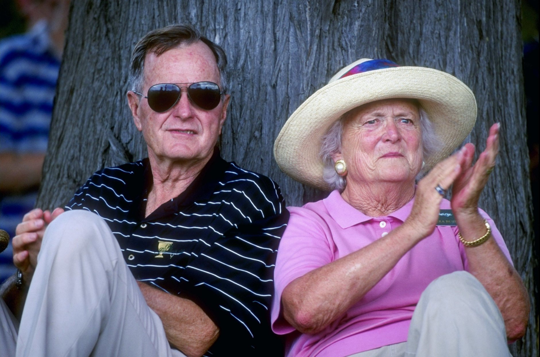 12 Dec 1998:  Former United States President George Bush sits by a tree with wife Barbra Bush as they watch the 1998 Presidents Cup at the Royal Melbourne Golf Course in Melborne, Australia. The International team defeated the U.S.A. team. Mandatory Credit: Nick Wilson  /Allsport