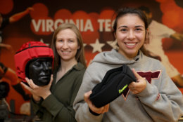 Abi Tyson, a Virginia Tech Helmet Lab research associate, and Megan Craig, a Helmet Lab intern, show off examples of protective soccer headgear. (Courtesy Virginia Tech)