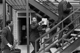 In this April 3, 1968 photo, the Rev. Dr. Martin Luther King Jr., center, and his aides walk at the Lorraine Motel, in Memphis, Tenn., discussing the restraining order King had just received barring them from leading another march in Memphis without court approval. On April 4, at 6:01 p.m., an assassin's bullet found Dr. King on the balcony of the Lorraine just outside his second-floor room, killing him. (Barney Sellers/The Commercial Appeal via AP)