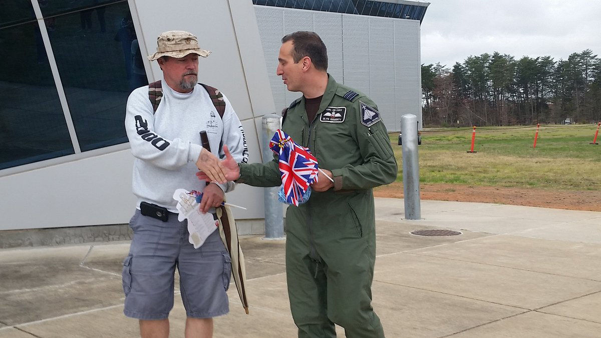 Glyn Gogherty, with the Royal Air Force handed out British flags to people at the Smithsonian's Air and Space Museum near Dulles Airport to celebrate the RAF's 100th birthday. (WTOP/Kathy Stewart)