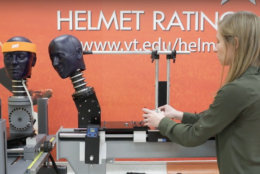 An impact simulator used in the study mimicked two players' heads colliding at three different impact speeds and two impact locations. The test dummy heads are pictured with Abi Tyson, Virginia Tech Helmet Lab research associate. (Courtesy Virginia Tech)