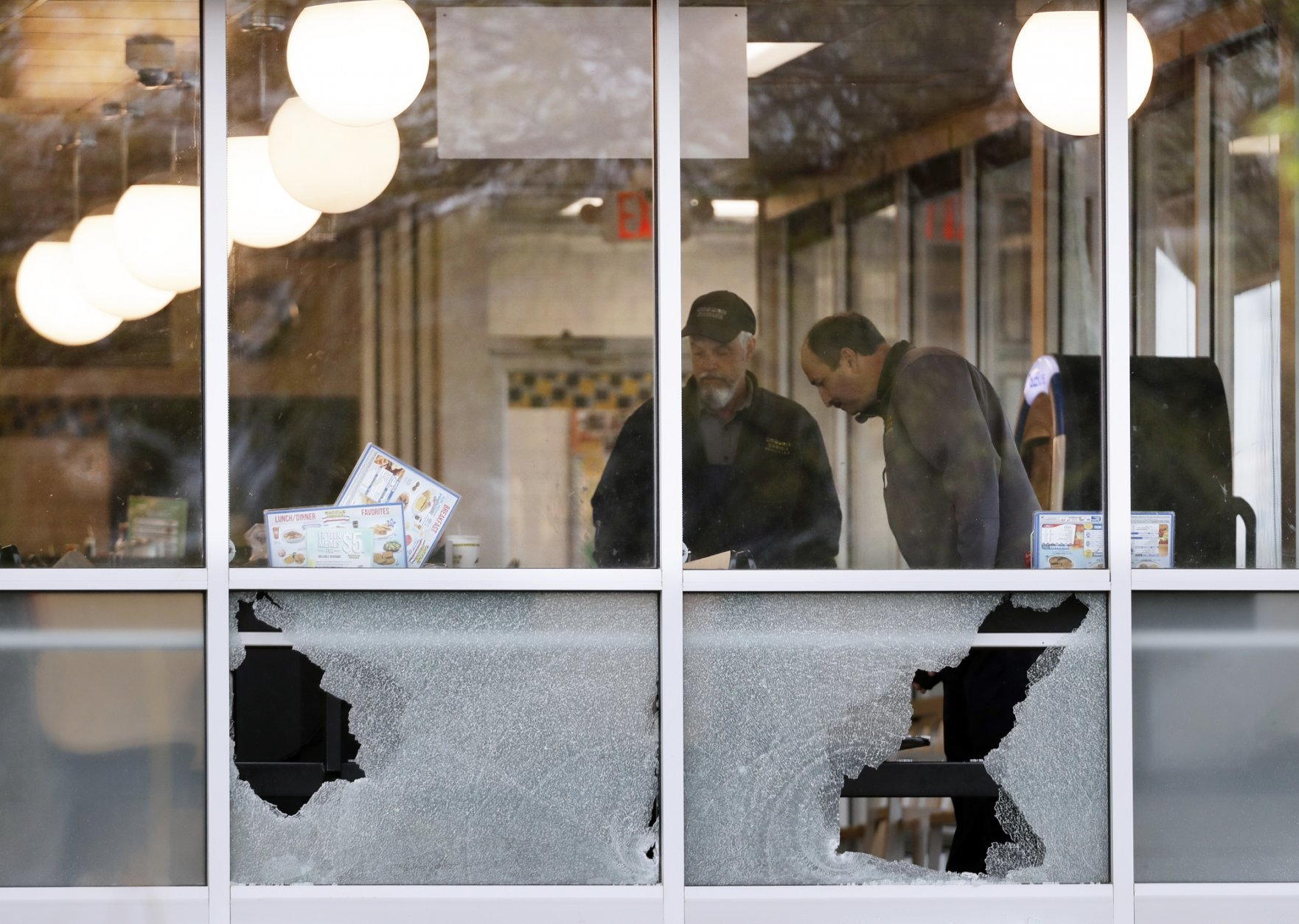 People look over the area near a window shot out at a Waffle House restaurant Sunday, April 22, 2018, in Nashville, Tenn. At least four people died after a gunman opened fire at the restaurant early Sunday. (AP Photo/Mark Humphrey)