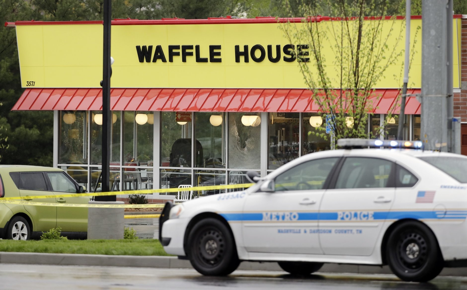A police car sits in front of a Waffle House restaurant Sunday, April 22, 2018, in Nashville, Tenn. At least four people died after a gunman opened fire at the restaurant early Sunday. (AP Photo/Mark Humphrey)
