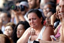 In this Saturday, April 7, 2018 photo, a supporter of Brazilian former President Luiz Inacio Lula da Silva cries as she listens to his speech, outside the Metal Workers Union headquarters in Sao Bernardo do Campo, Brazil. Da Silva told supporters he will comply with an arrest warrant and turn himself in to police, to begin serving a sentence of 12 years and one month for a corruption conviction. (AP Photo/Andre Penner)