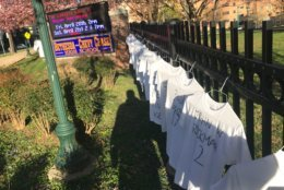 T-shirts, each inscribed with the name and age of a 2018 gun violence victim hangs on the fence, along busy East-West Highway. (WTOP/Neal Augenstein)