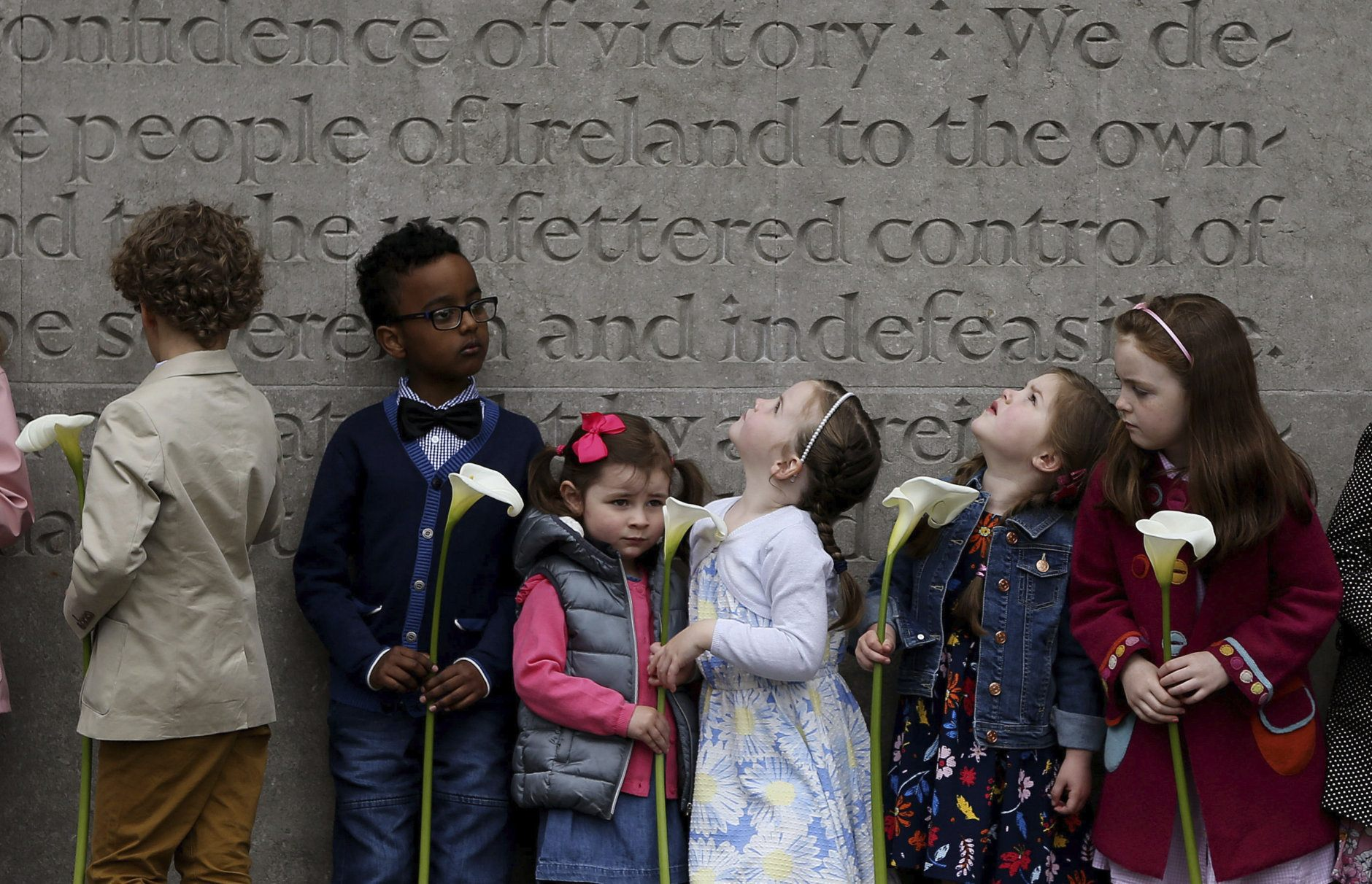 Children wait to place an Easter Lily, a symbol of the 1916 Easter Rising, at Arbour Hill cemetery in Dublin, Ireland, during the annual Fianna Fail 1916 Easter Rising commemoration, Sunday April 22, 2018. (Brian Lawless/PA via AP)