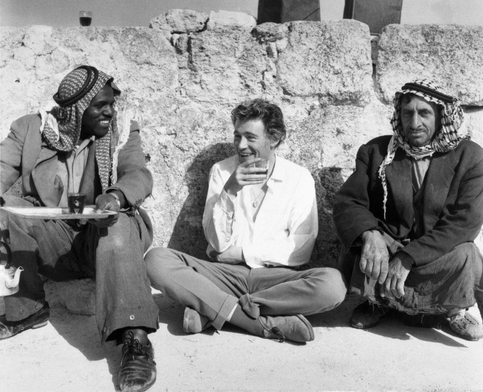 "Peter O'Toole, center, the Irish actor who is to play the title role in the film ""Lawrence of Arabia"" squats on the dusty ground as he takes a glass of tea with a couple of Beduin farmers on April 20, 1961 in Amman, Jordan. O'Toole has spent several weeeks among the Jordanian Arabs learning their language, local customs and how to ride a camel. (AP Photo)"