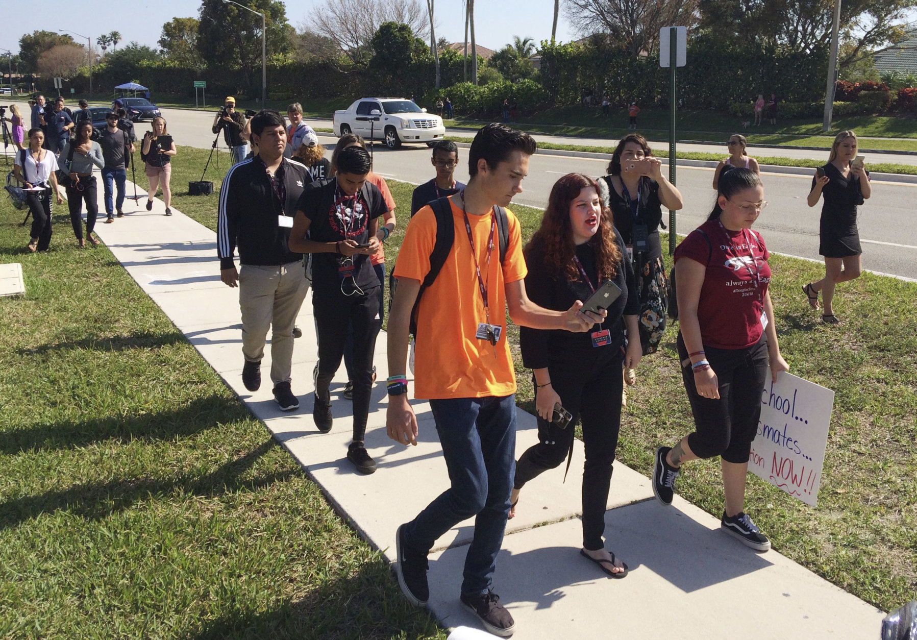 David Hogg, left, a student activist from Marjory Stoneman Douglas High School speaks to a student as they walk out of their school, Friday, April 20, 2018 in Parkland, Fla.  Another wave of student walkouts is expected to disrupt classes Friday at hundreds of schools across the U.S. as young activists press for tougher gun laws. The protests were chosen to line up with the 19th anniversary of the Columbine High School shooting, which left 13 people dead in Littleton, Colorado. At 10 a.m., students plan to gather for moments of silence honoring the victims at Columbine and other shootings. (AP Photo/Terry Spencer)