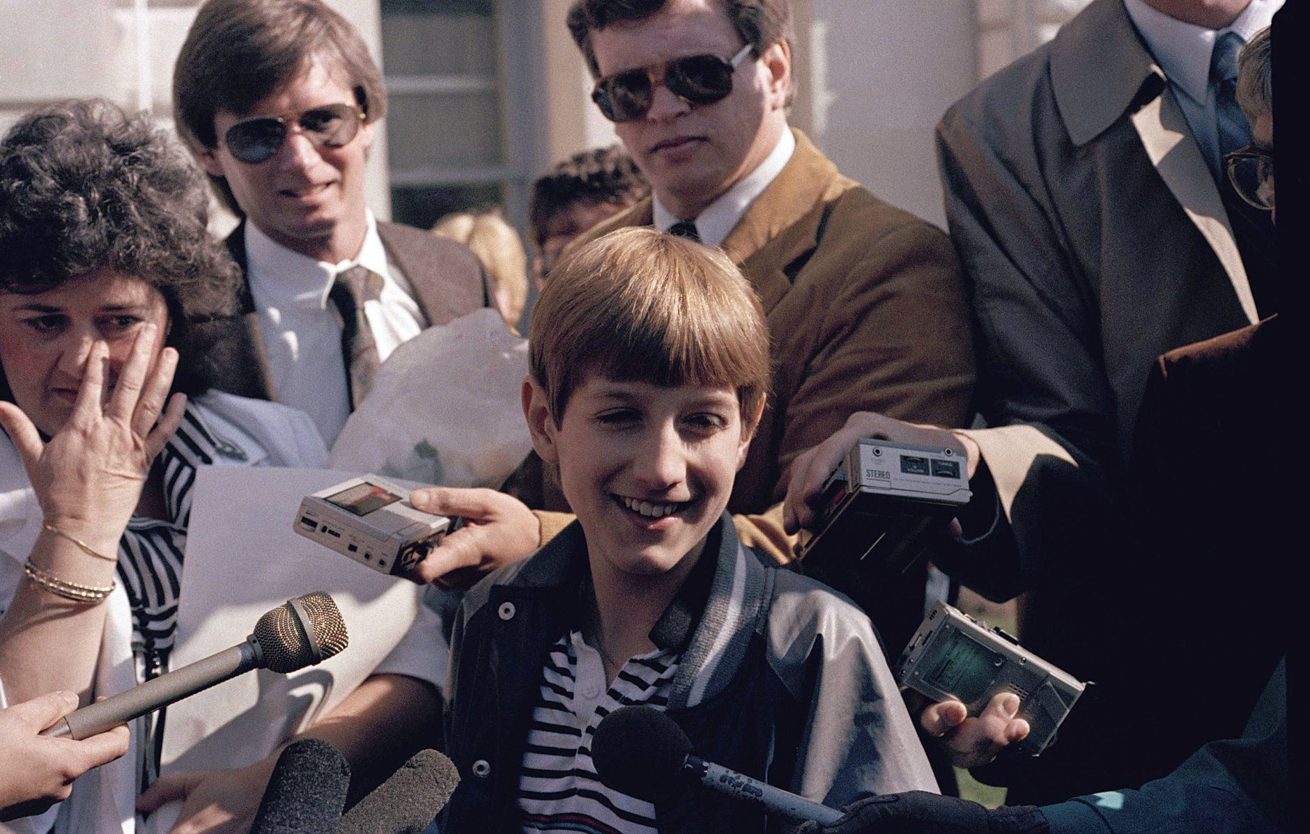 Teenage AIDS victim Ryan White is surrounded by friends and reporters after a judge threw out a temporary injunction barring him from attending classes at Western Middle School near Kokomo, Ind., April 10, 1986. Ryan's mother Jeanne is at left and attorney Charles V. Vaughn is at rear.  (AP Photo)