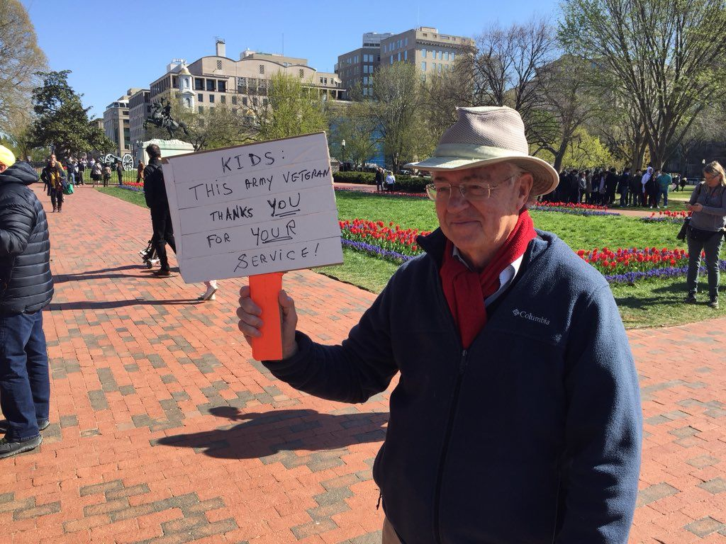 "At the walkout protest, a man holds up a sign that reads, ""Kids: This Army veteran thanks you for you service!"" (WTOP/John Domen)"