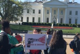 "A student protester holds a sign that says, ""Enough is enough"" in front of the White House. (WTOP/John Domen)"