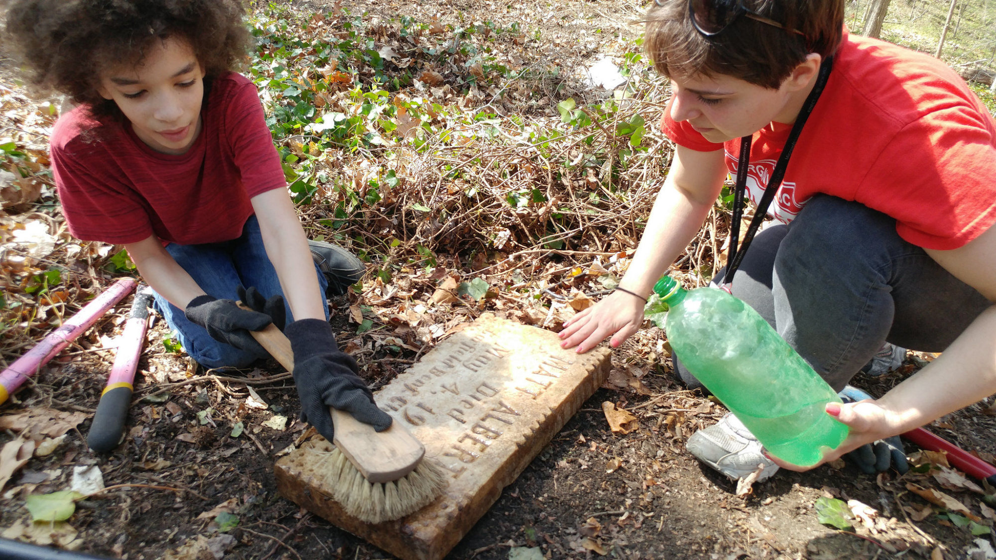 Volunteers clean an uncovered headstone at East End Cemetery. (Photo credit: George Copeland Jr.)