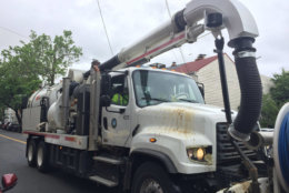 A machine to suck leaves out of gutters in Alexandria. (WTOP/Kristi King)