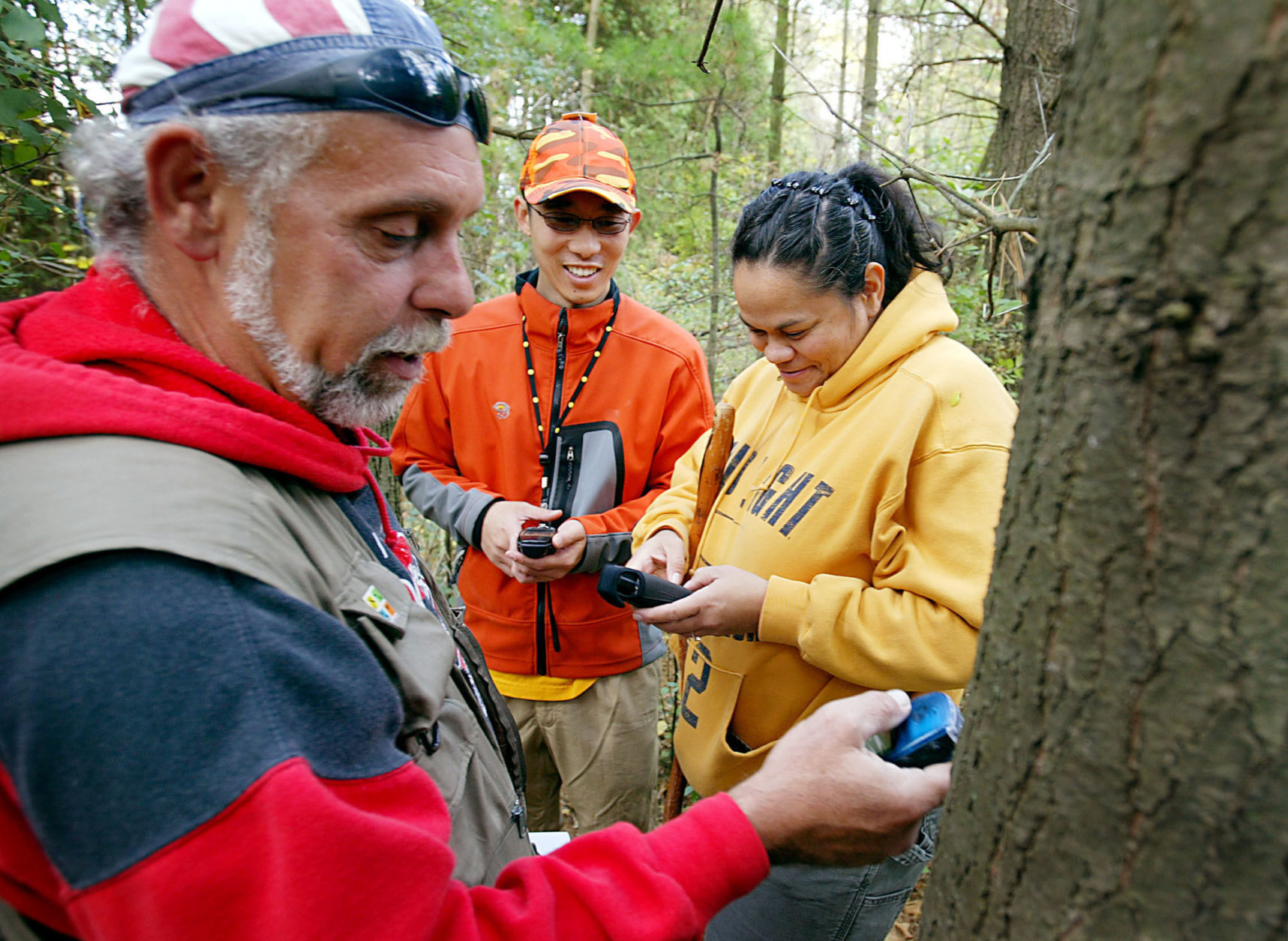 Geocachers Bob Rathbone, left, Robin Bright, right, and new geocacher Sang Park, center, program the next destination into their GPS units, while searching for caches in the New Munster Wildlife Park, Friday October 21, 2005 in New Munster, Wisconsin.  An estimated one million people worldwide have played the scavenger hunt game that has a high-tech twist. In fact, geocaching is becoming popular enough that numerous states now post online the coordinates of local sites of interest to encourage state tourism. (AP Photo/ Ron Kuenstler)