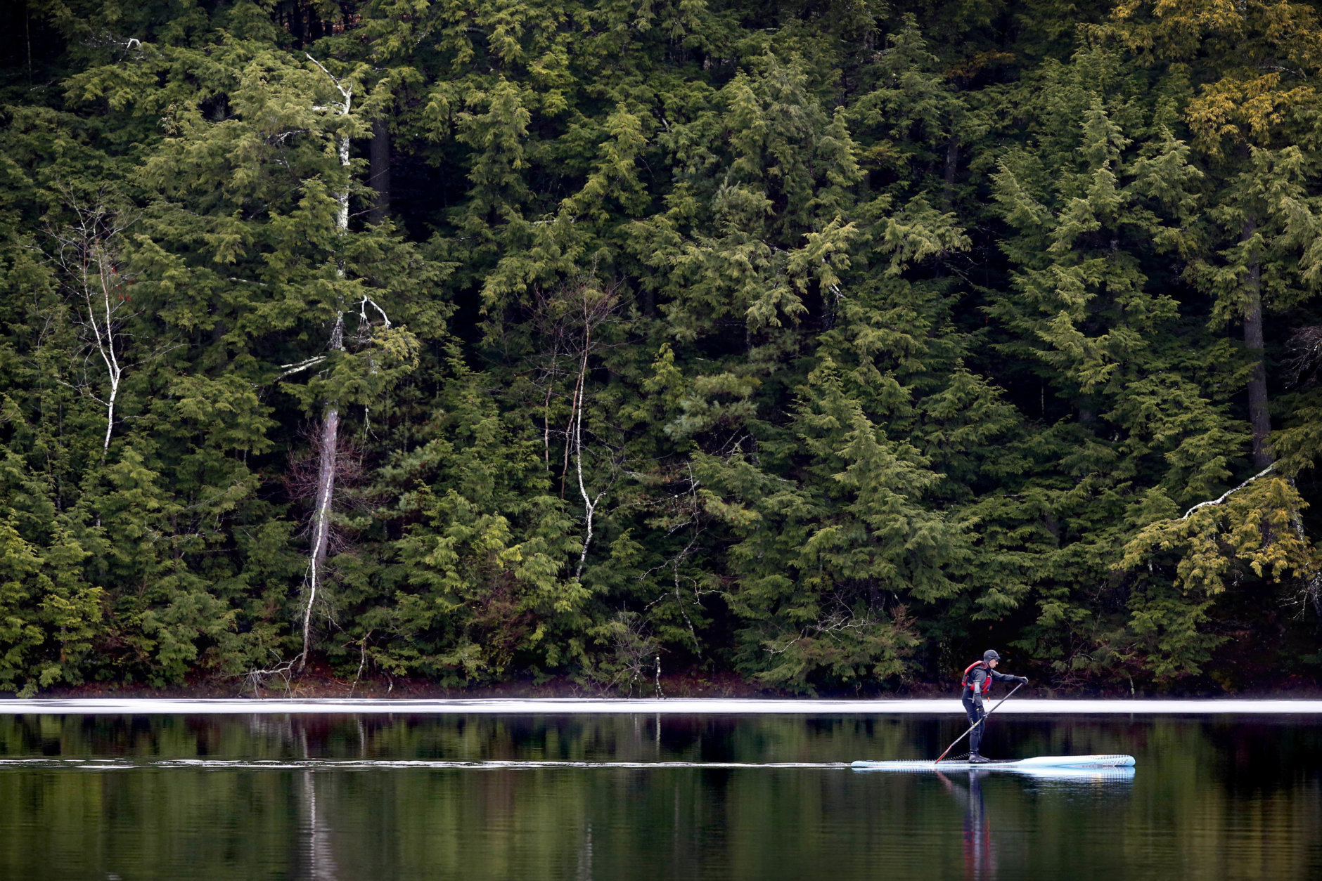 Jeff Warren of Auburn, Maine glides across Lower Range Pond on his paddleboard, Thursday, March 17, 2016, in Poland, Maine. (AP Photo/Robert F. Bukaty)