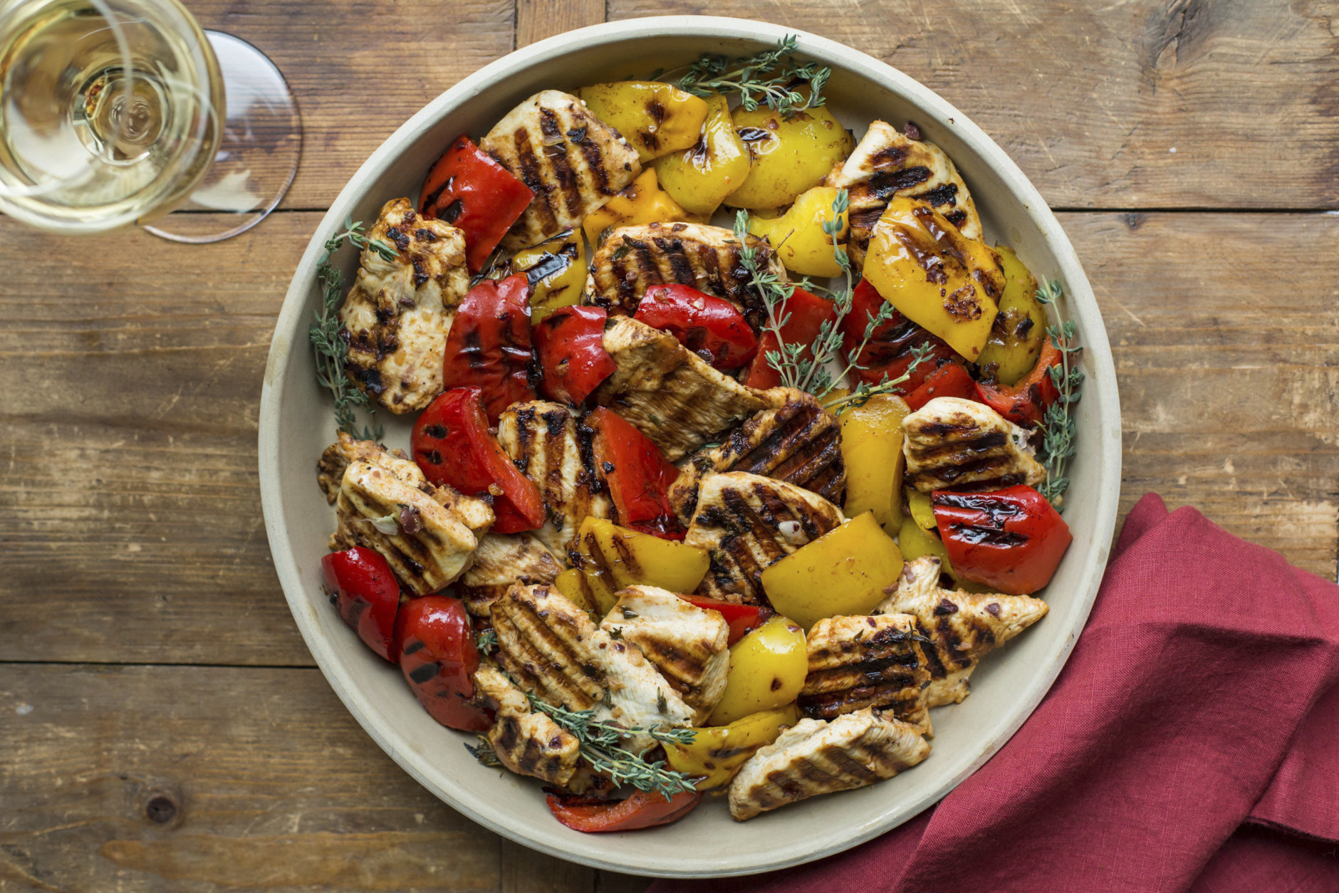 This April 2017 photo shows grilled lemony chicken and peppers in New York. This dish is from a recipe by Katie Workman. (Sarah Crowder via AP)