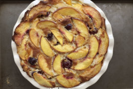 This July 22, 2017 photo shows a summer peach clafoutis in Houston, Texas. This dish is from a recipe by Elizabeth Karmel. The recipe that can be tailored to whatever summer fruit is on hand, and not just cherries, which are traditionally used in France for this rustic dessert that envelopes the fruit in a custardy crepe-like batter. (Elizabeth Karmel via AP)
