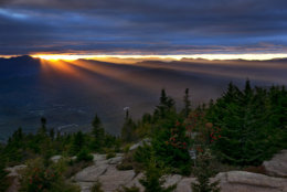 Sun rays spill through a gap between the clouds and the White Mountains as the skies begin to clear above Bartlett, N.H., Friday, Sept. 22, 2017. The first weekend of autumn is expected to be unusually warm with temperatures expected to reach the upper 80s. (AP Photo/Robert F. Bukaty)