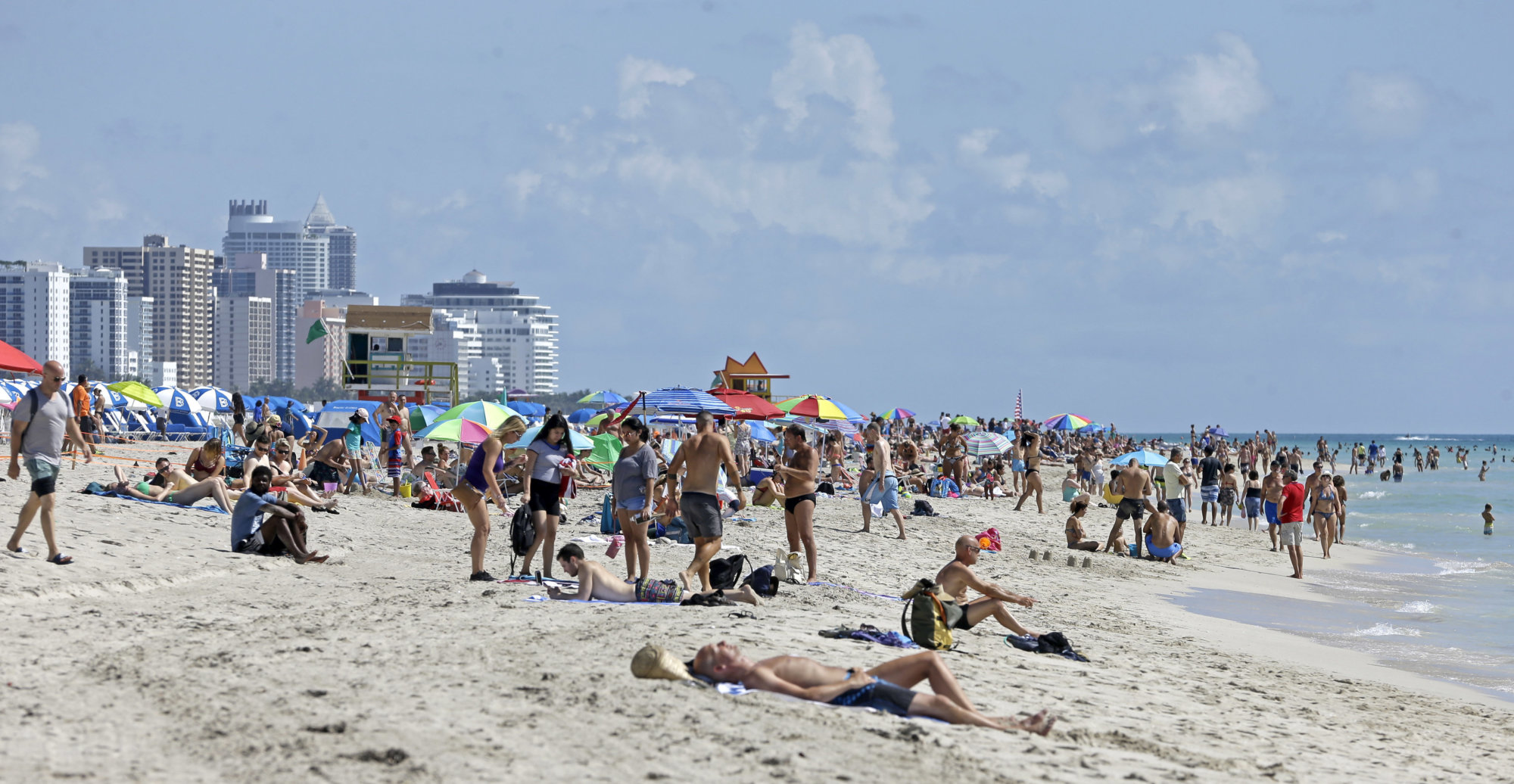 FILE - In this Aug. 2, 2017, file photo, local residents and tourists enjoy a day at the beach in the South Beach area of Miami Beach, Fla. South Beach can be a great place for parents and teens to vacation together, especially if they can go their separate ways at times for beach, pool, shopping and dining. (AP Photo/Alan Diaz, File)