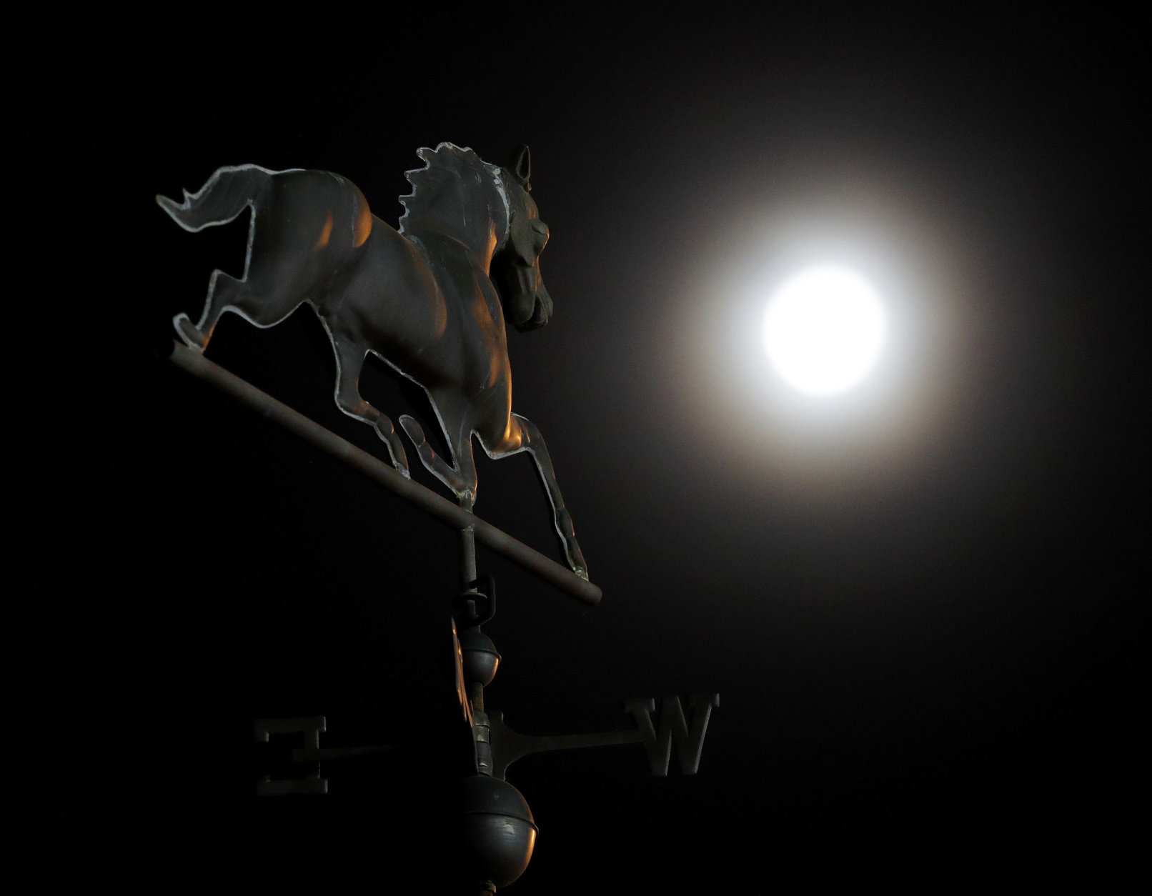 The waning full moon shines on a weather vane during a morning workout at Churchill Downs Wednesday, May 2, 2018, in Louisville, Ky. The 144th running of the Kentucky Derby is scheduled for Saturday, May 5. (AP Photo/Charlie Riedel)