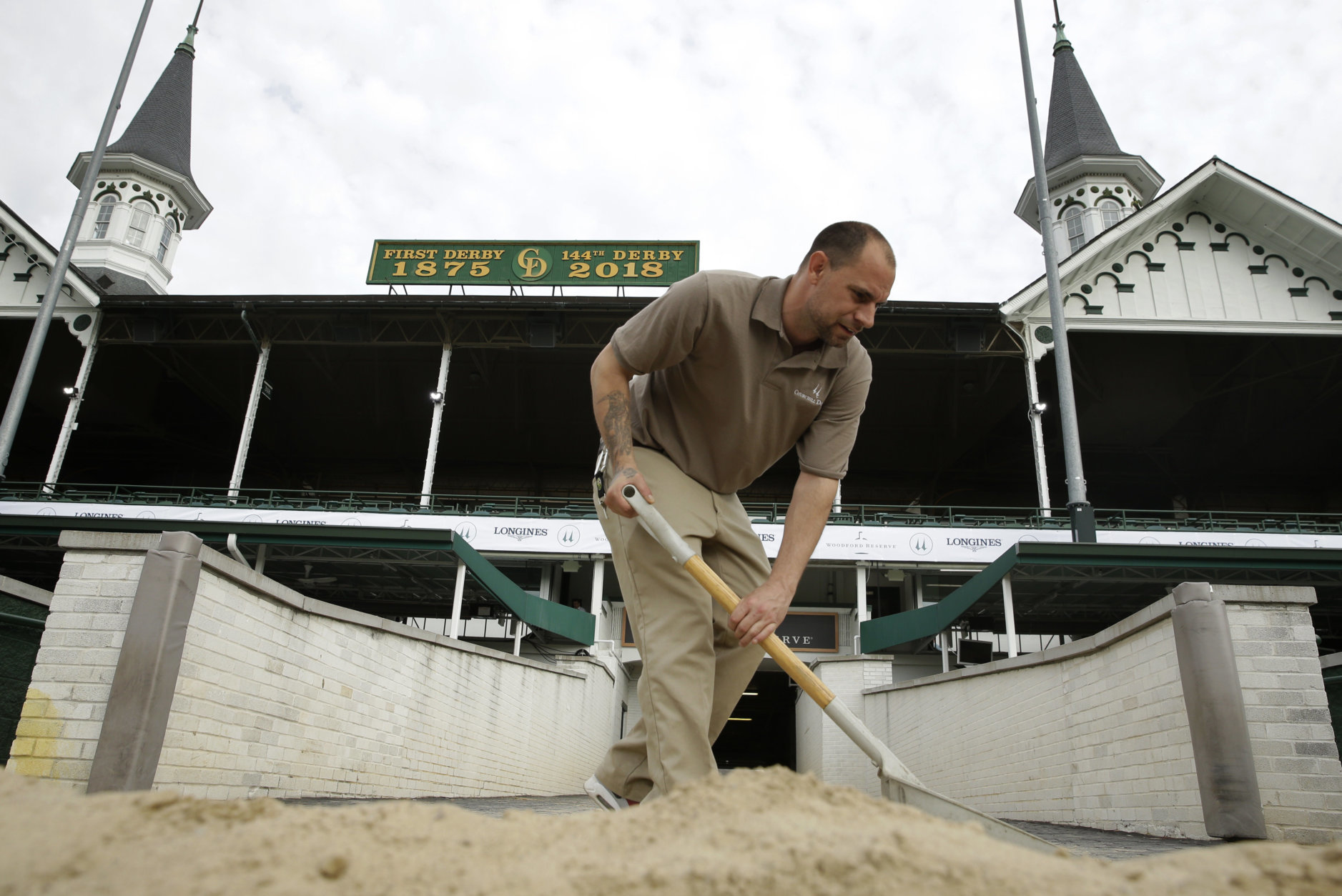 A worker scoops dirt back onto the track after morning training for race horses at Churchill Downs Wednesday, May 2, 2018, in Louisville, Ky. The 144th running of the Kentucky Derby is scheduled for Saturday, May 5. (AP Photo/Charlie Riedel)