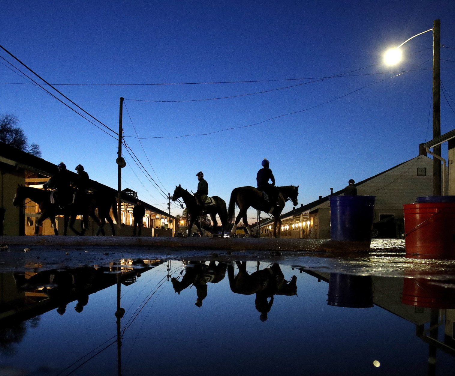 Horses make their way back to the barn after an early morning workout at Churchill Downs Monday, April 30, 2018, in Louisville, Ky. (AP Photo/Charlie Riedel, File)