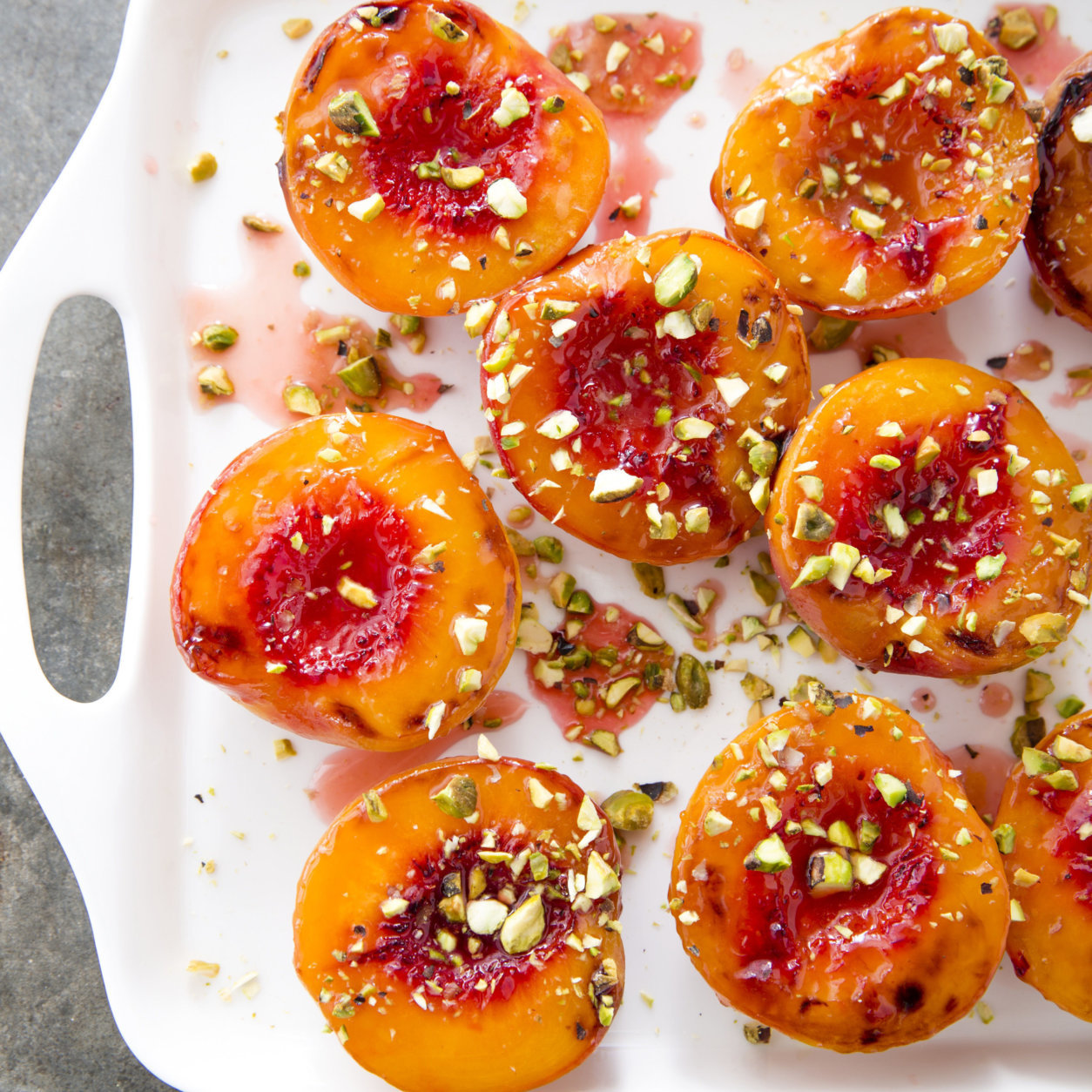 "This undated photo provided by America's Test Kitchen in May 2018 shows honey glazed roasted peaches in Brookline, Mass. This recipe appears in the cookbook ""How to Roast Everything."" (Joe Keller/America's Test Kitchen via AP)"