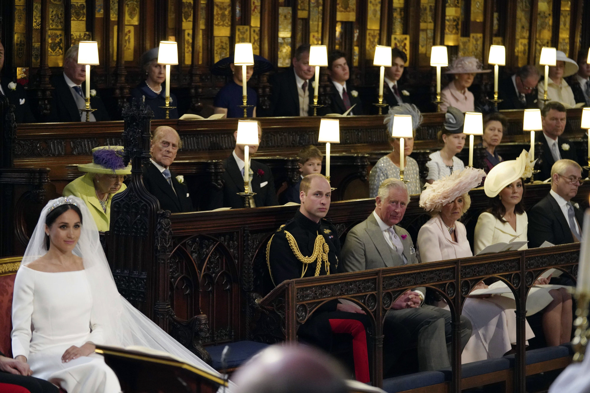 Meghan Markle, left, is watched by middle row from left, Queen Elizabeth, Prince Philip, Prince Edward, James, Viscount Severn, Sophie Countess of Wessex, Lady Louise Mountbatten-Windsor, Princess Anne and Tim Laurence, front row from left, Prince William, Prince Charles, Camilla Duchess of Cornwall, Kate Duchess of Cambridge and Prince Andrew during the wedding ceremony of Prince Harry and Meghan Markle at St. George's Chapel in Windsor Castle in Windsor, near London, England, Saturday, May 19, 2018. (Jonathan Brady/pool photo via AP)