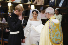 Britain's Prince Harry and Meghan Markle hold hands in St George's Chapel at Windsor Castle during their wedding service, conducted by the Archbishop of Canterbury Justin Welby in Windsor, near London, England, Saturday, May 19, 2018. (Dominic Lipinski/pool photo via AP)